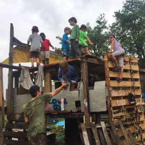 Children playing on a wood fort built from scrap materials