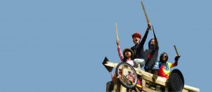 children standing on prow of play boat being pirates, swords held aloft