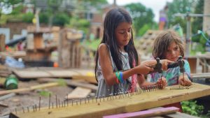 Two young girls hammering nails into wood.