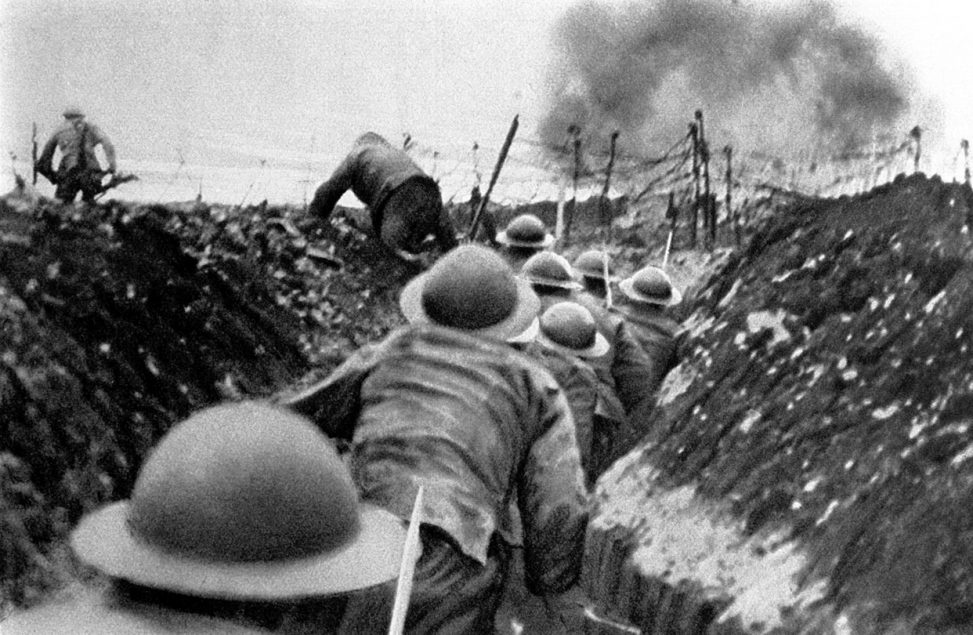 Black and white photo of troops moving in a trench. Explosion ahead.