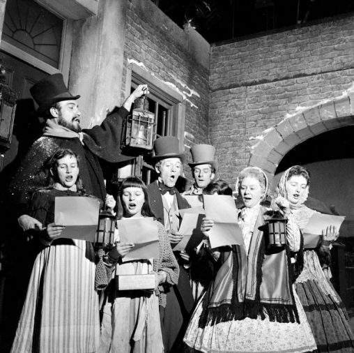 black and white image of carol singers in historic clothing
