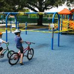 """Children on bikes observing playground equipment wrapped with """"do not use"""" tape"""