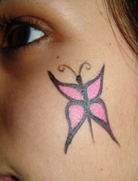 Butterfly face painted on a childs cheek