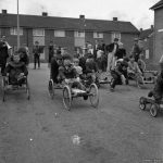 Old black and white photo of groups of children on homemade go-karts. Credits: Media Wales